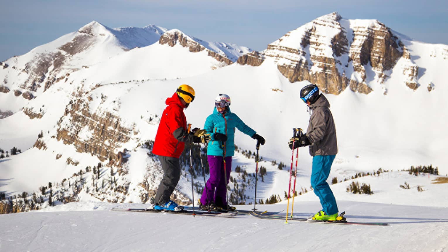 Three people in colourful snowsuits, helmets, skis stand on snow at top of slope on mountain