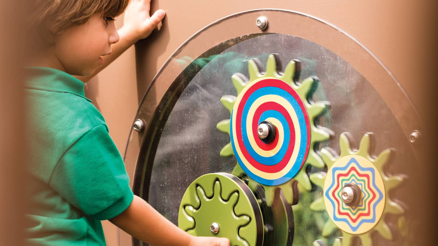 Young boy spins colourful wheel in Discovery Children's Museum