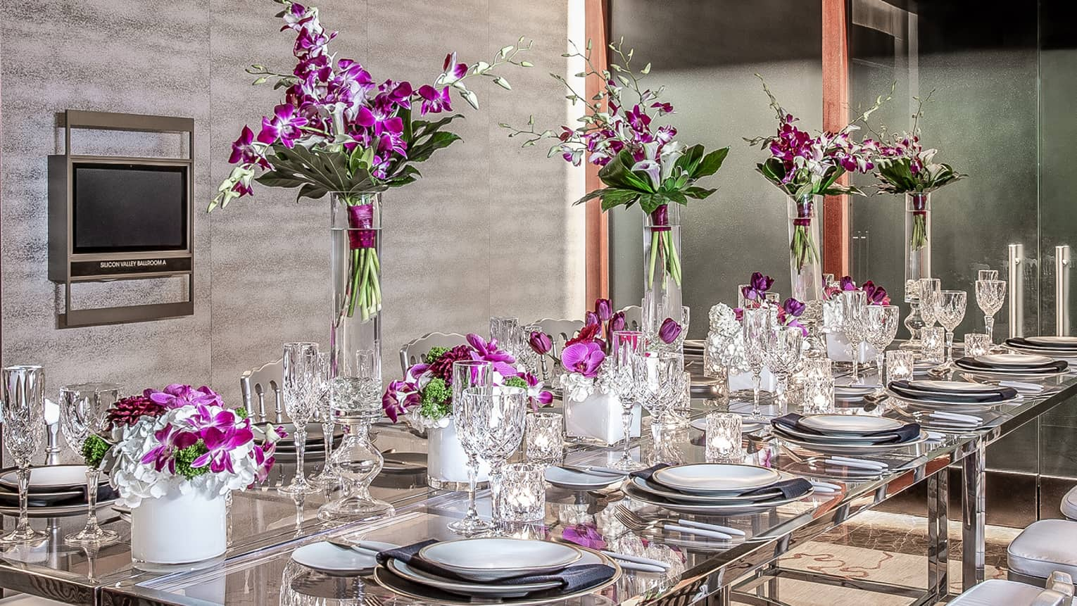 Purple flowers, goblets and place-settings decorate a glass able in an event space