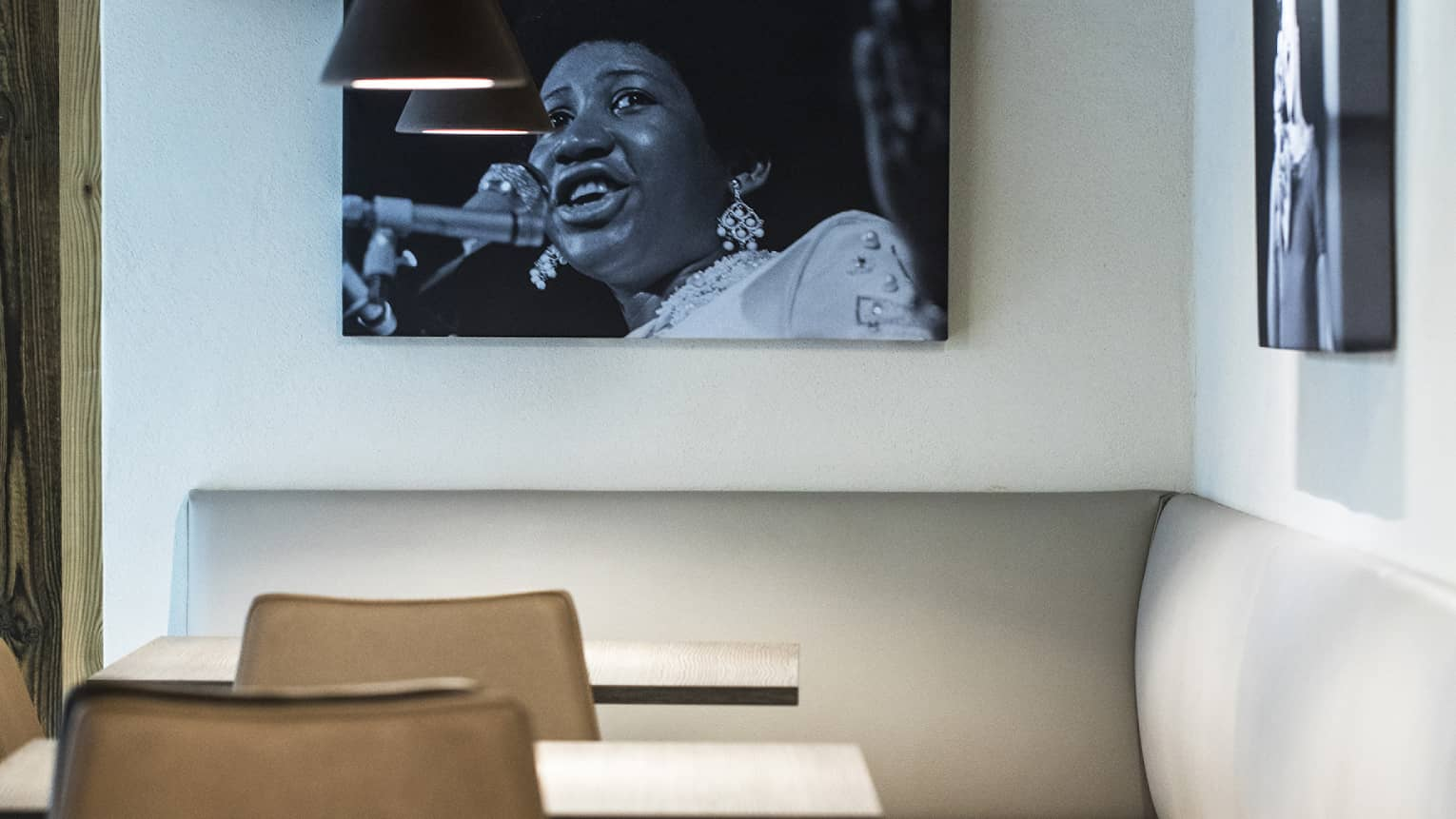 Two small tables with chairs and white banquette in modern bar with black fixtures, white walls and a hanging black-and-white portrait of Aretha Franklin