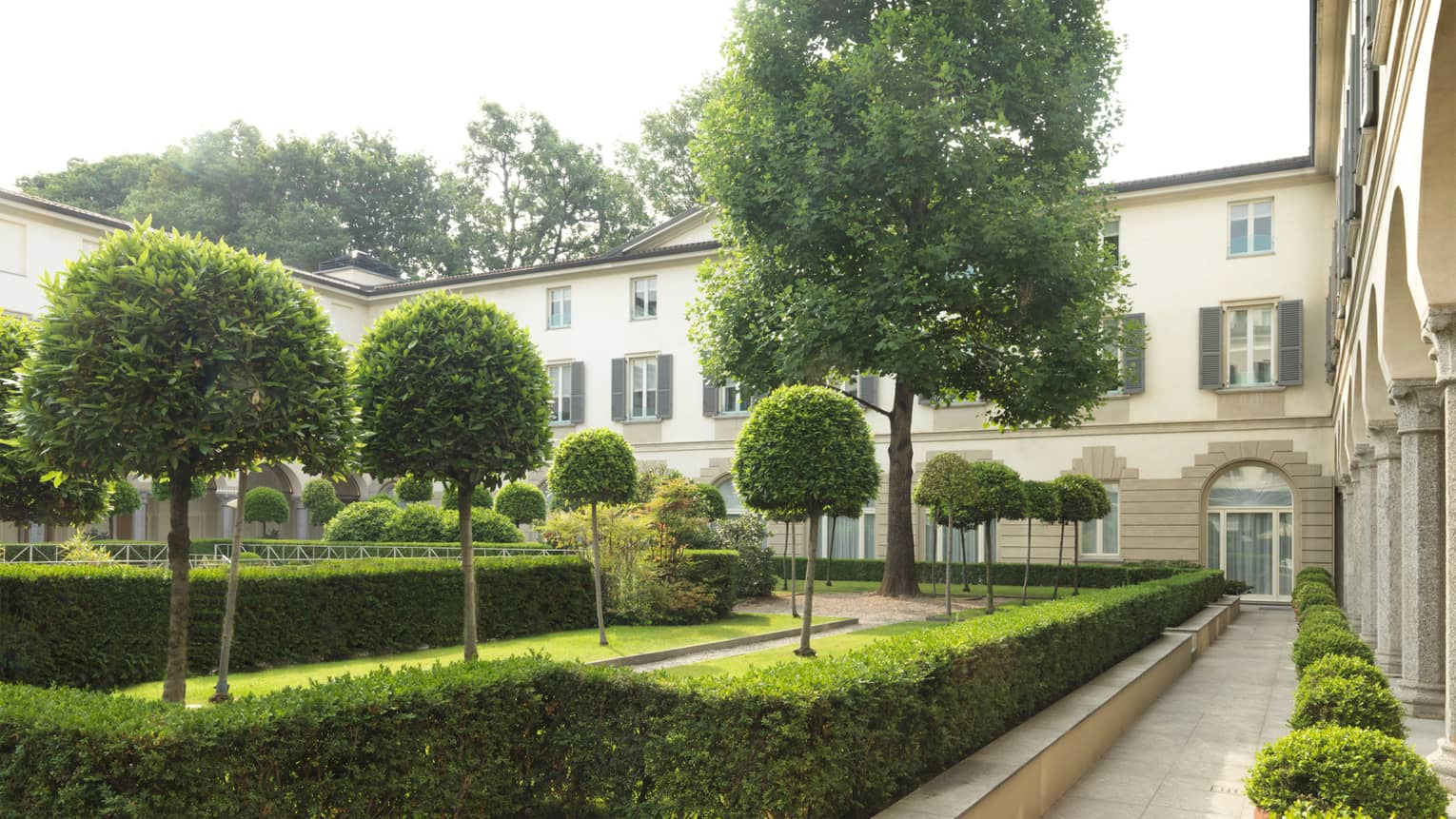 Trees, shrubs along landscaped courtyard by Four Seasons Hotel Milan building