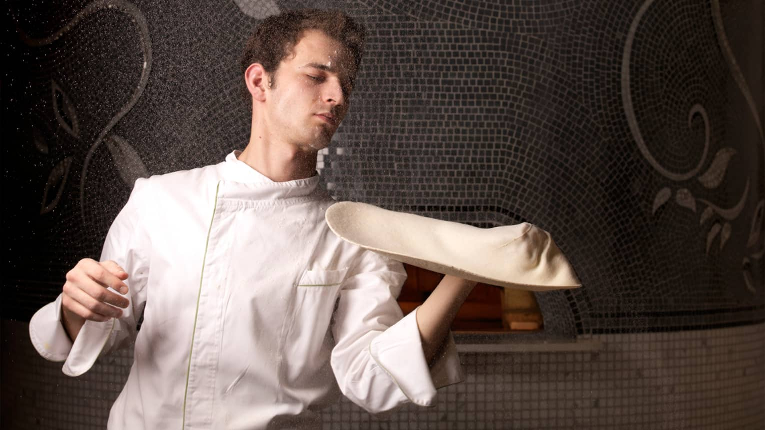Chef in white uniform tosses pizza dough on hand in front of black mosaic tile wall