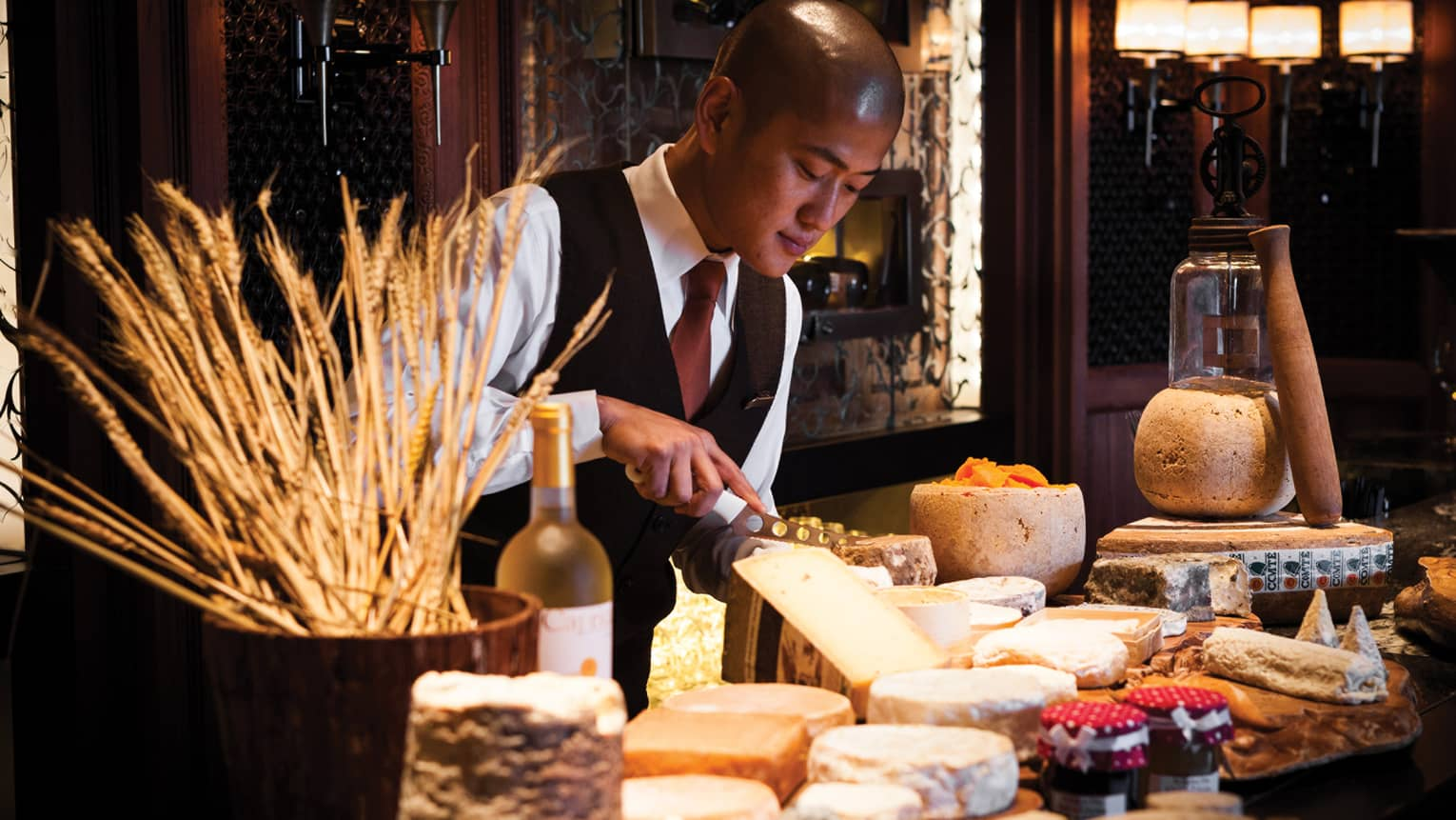Hotel staff in vest slices large wedge of cheese on counter with cheeses, jams