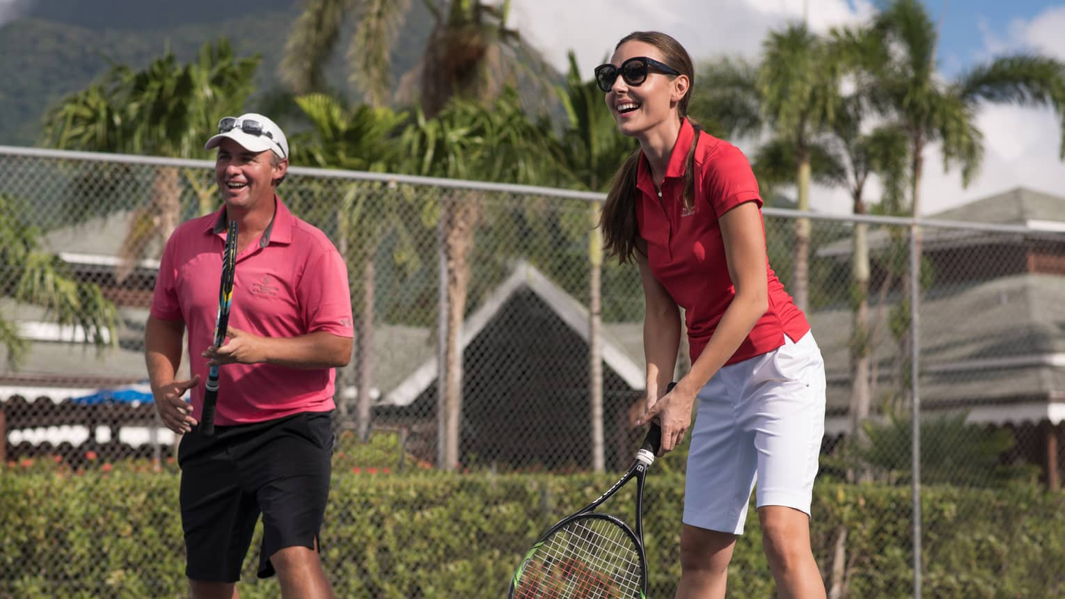 Smiling man and woman with tennis rackets on court