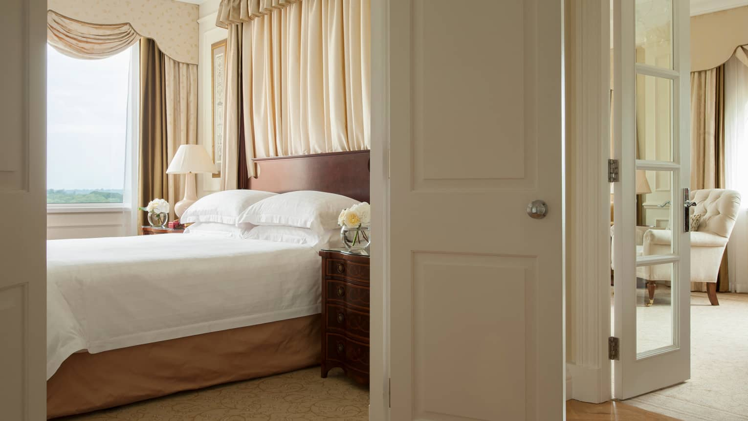 Open white door to sunny hotel bedroom, bed by window