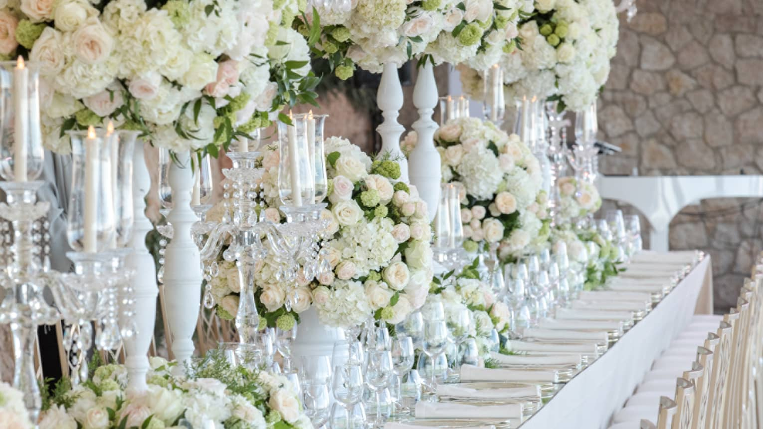 Elegantly set white banquet table lined with chairs, tall white and pink floral arrangements, candles
