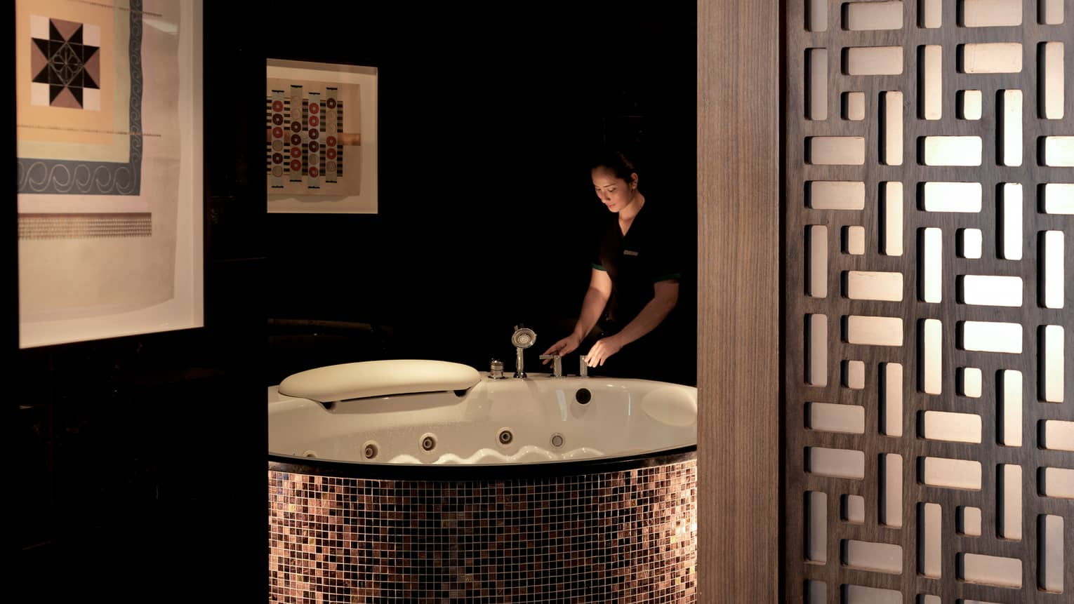 Woman holds taps of large round bathtub with tiles in dimly-lit spa room with wood room divider