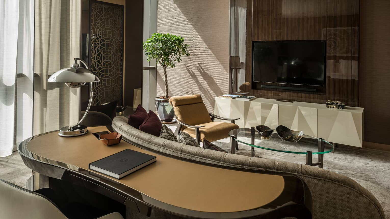 Studio Suite Burj Khalifa View room large curved work desk, lamp behind sofa, glass coffee table, armchair