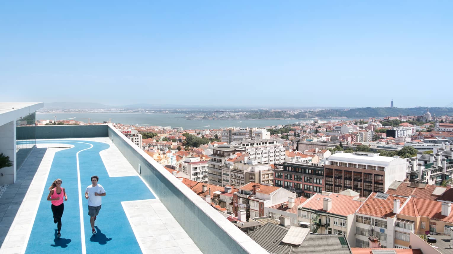 Two people run on blue, rooftop running track, overlooking Lisbon