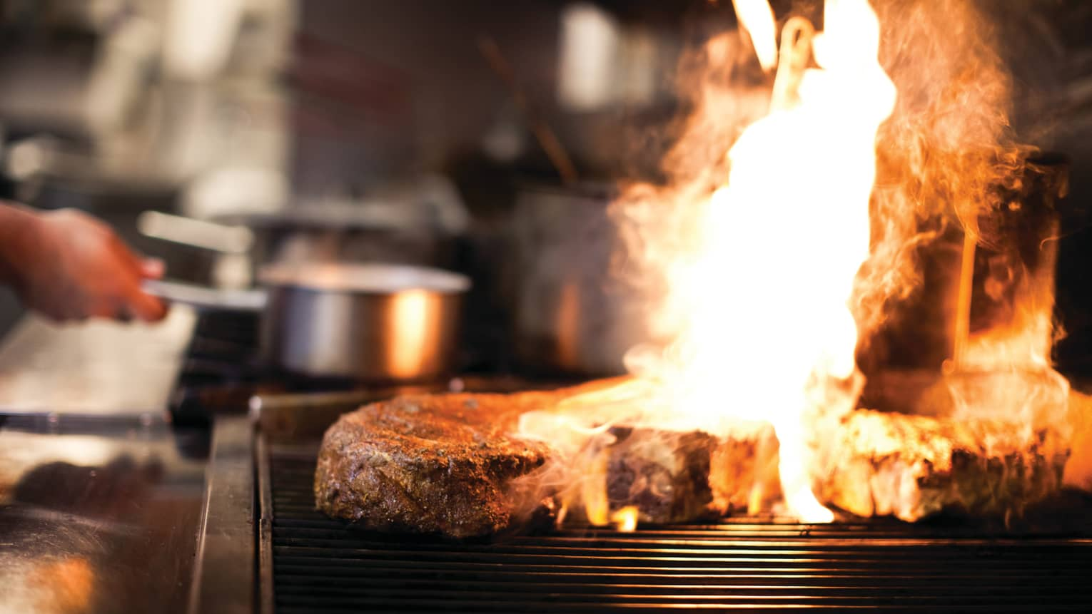 Orange flames shoot up from grill over large steak in Sidecut kitchen