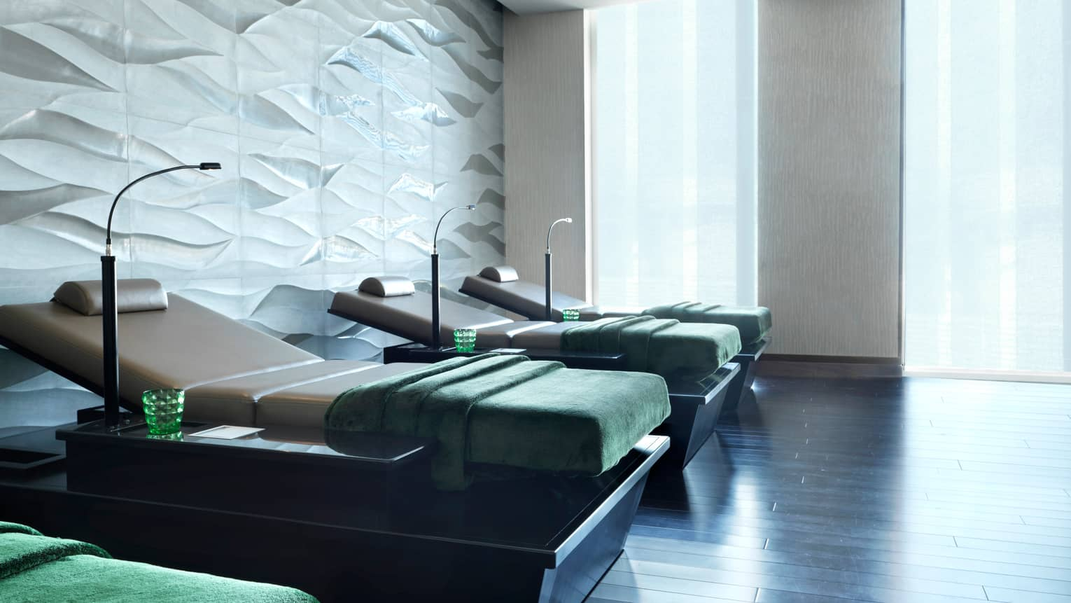 Four spa beds side-by-side with reading lamps, green blankets and glasses, in front of white wall and sunny windows