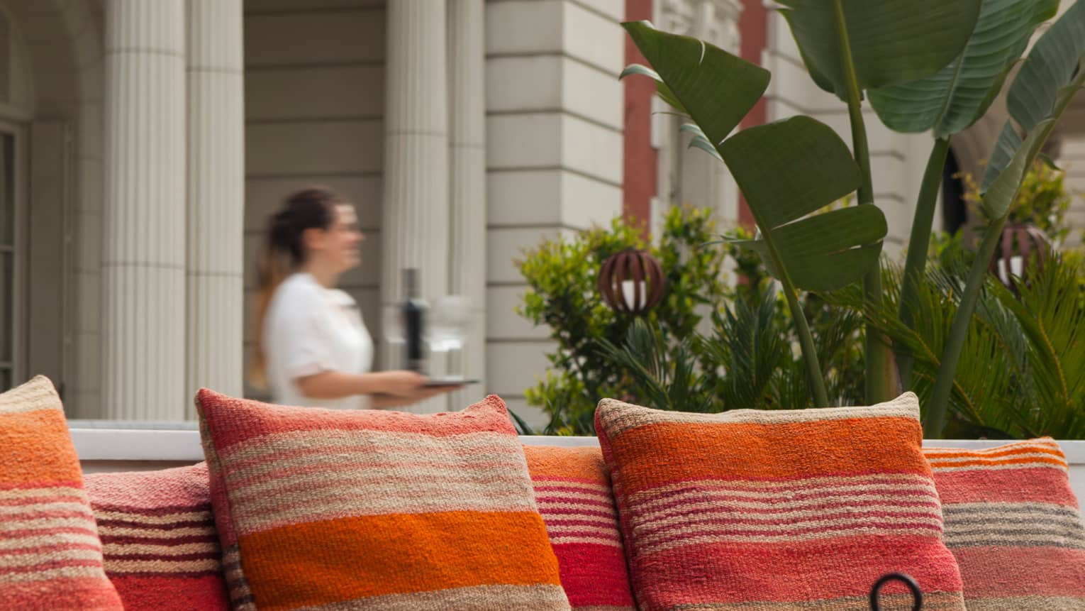 Close-up of striped orange patio pillows, server walking in background with tray