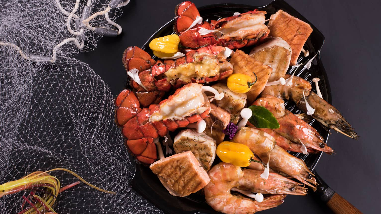 Seafood night platter in iron pan with rows of grilled jumbo shrimp, lobster tails, tuna fillets, whole yellow peppers
