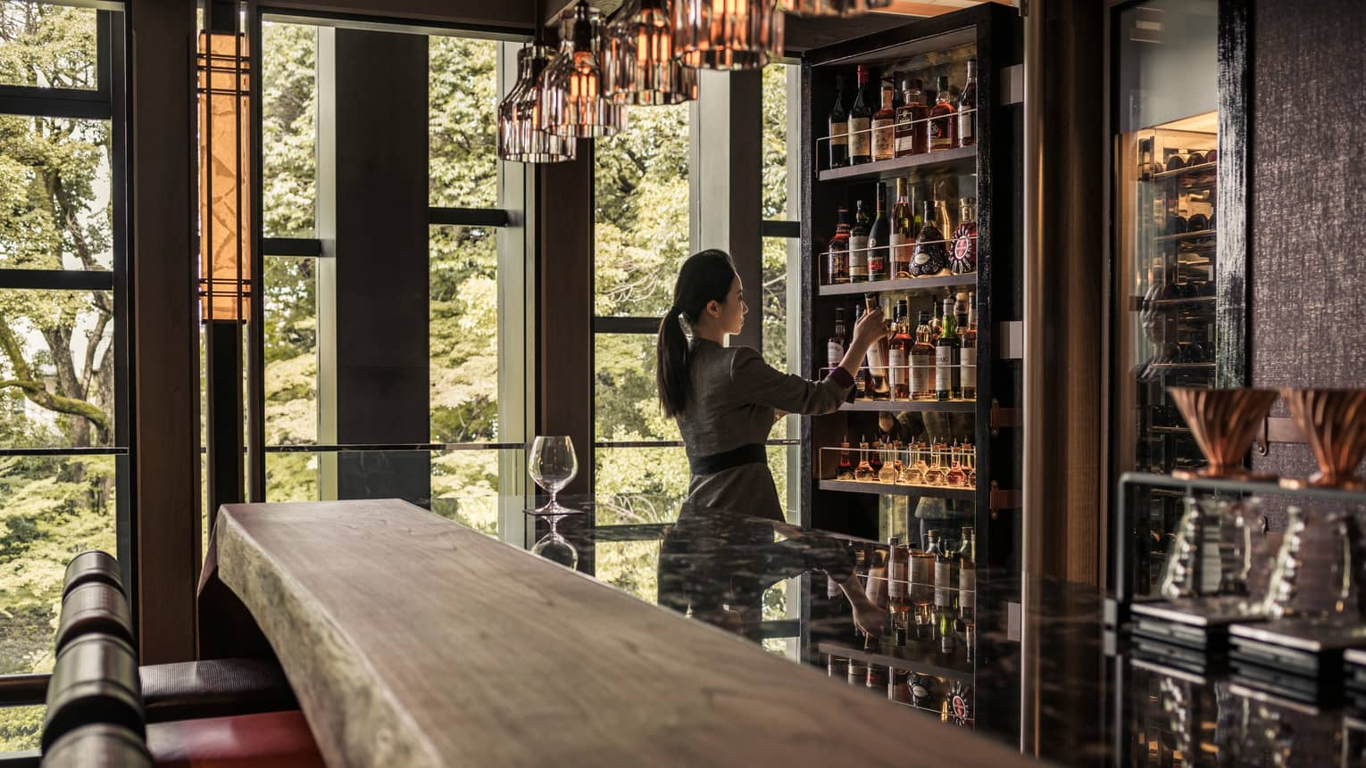 Lounge bartender retrieves bottle on wine from cellar behind long rustic wood bar