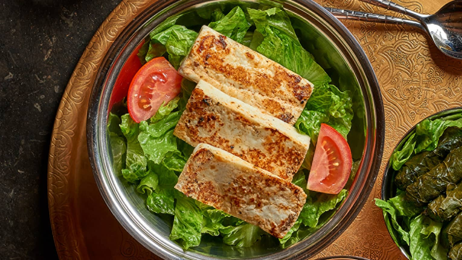Three strips of fried Halloumi cheese on bed of lettuce in bowl, tomato wedge