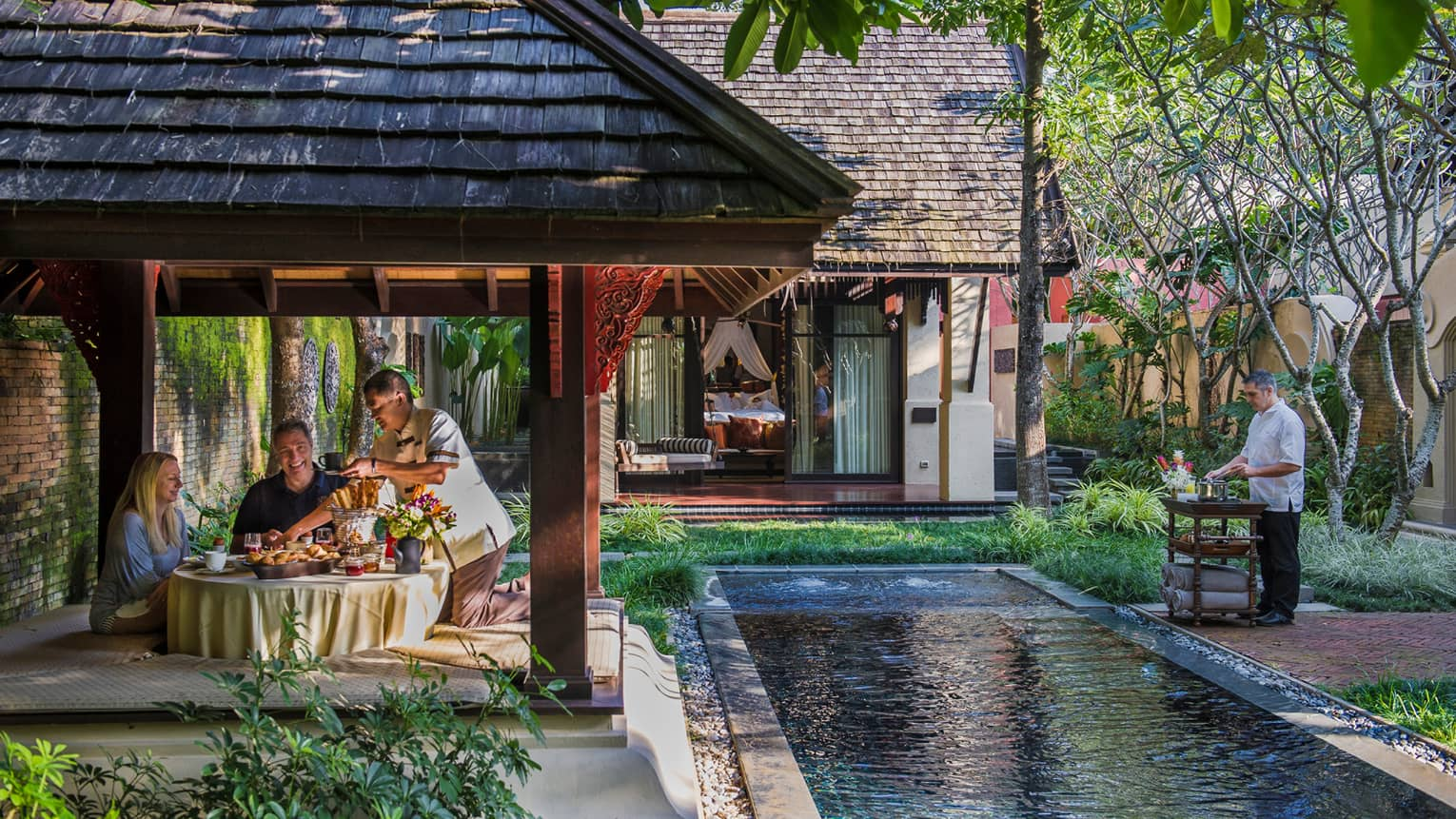 Staff serve couple under covered dining gazebo by long villa pool