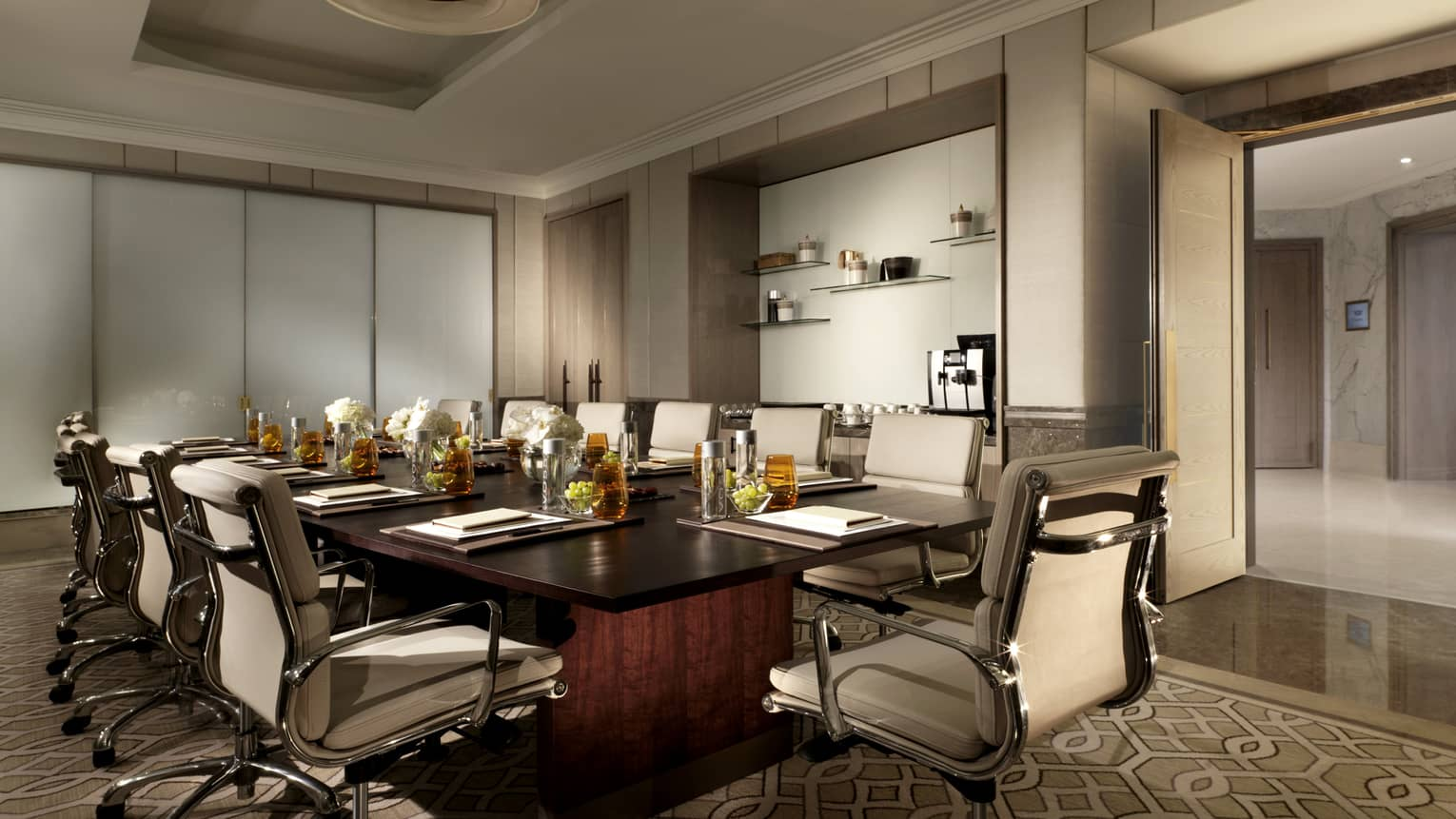 Meeting room with white leather executive swivel chairs around large wood boardroom table with amber glassware