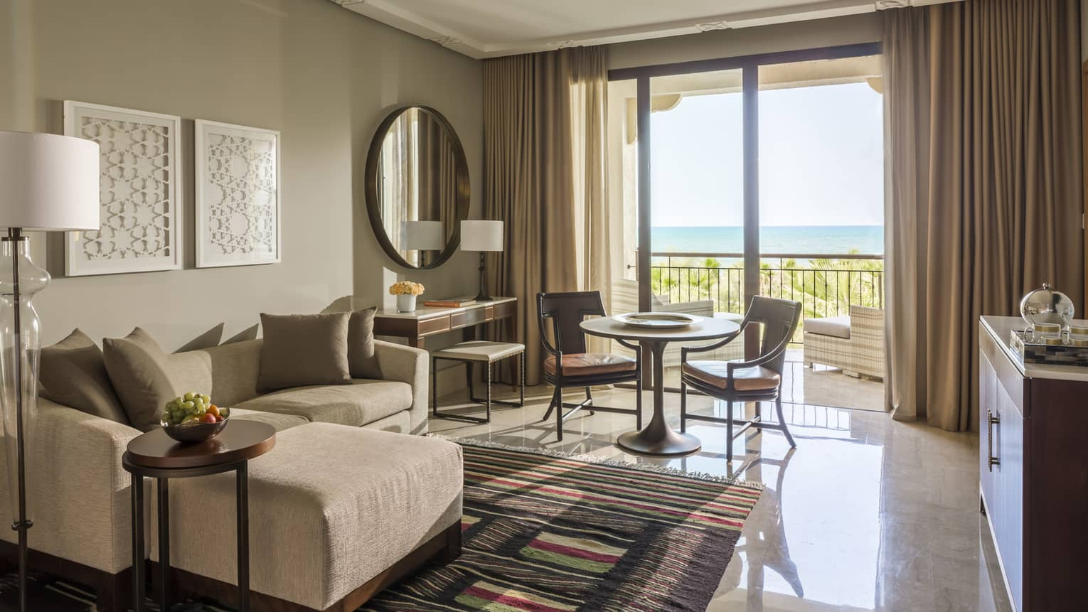 Deluxe Sea View hotel room with modular sofa, small table and chairs by sunny balcony doors