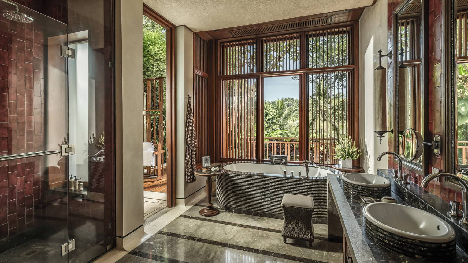 A sunlit bathroom with a tub and two sinks