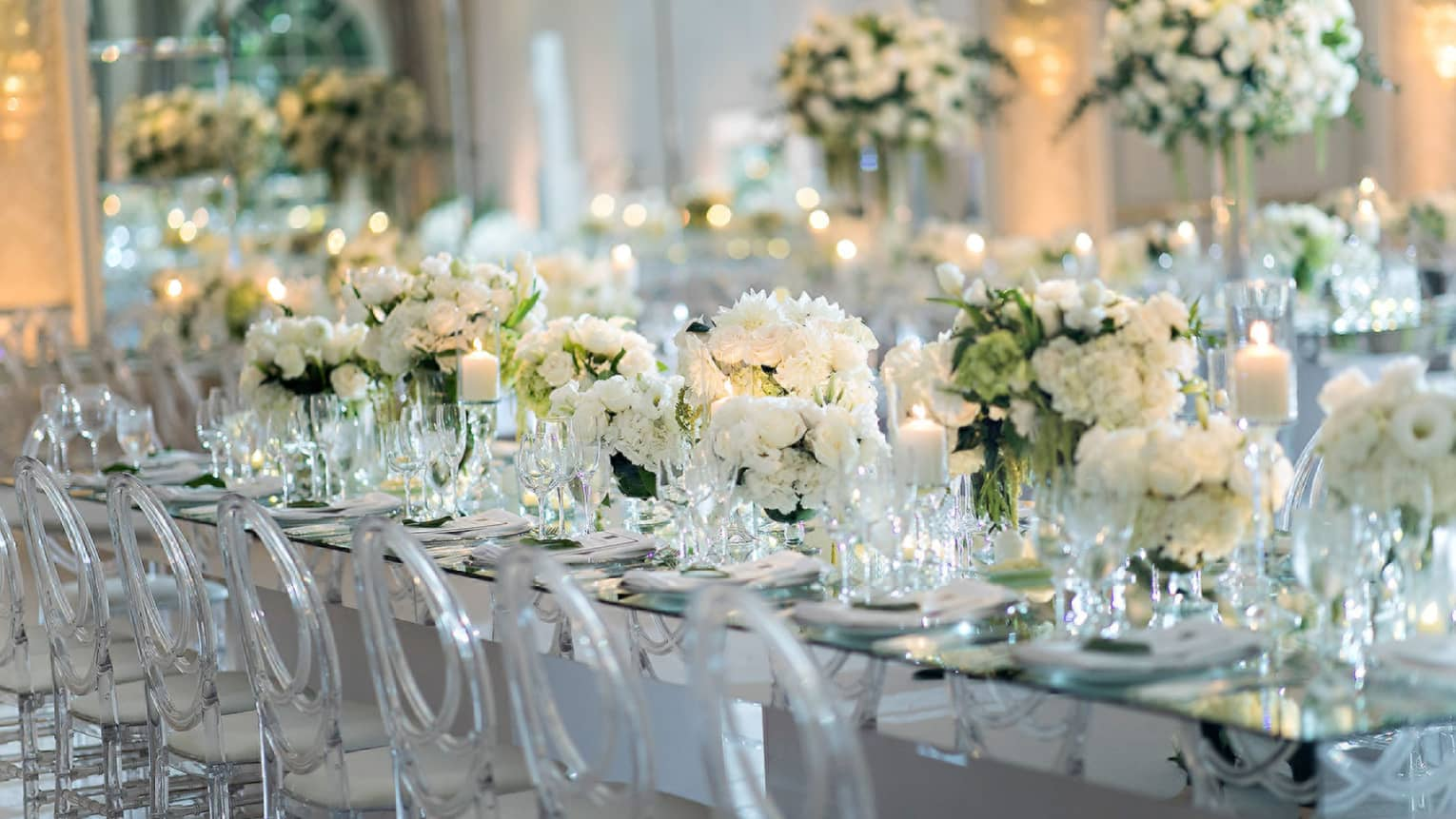 Long wedding dining table filled with white flowers, lined with transparent chairs