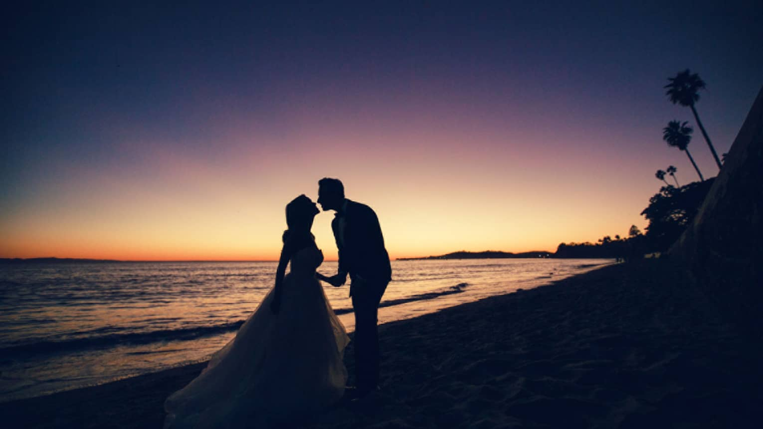 Silhouette of bride and groom leaning in for a kiss on beach at sunset