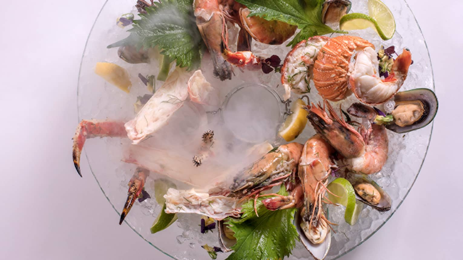 Grilled lobster tails, crab legs, oysters in ring on glass plate