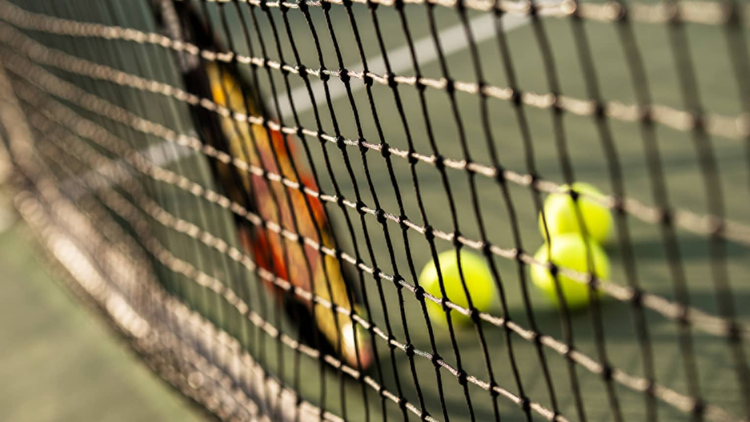 Close-up of tennis racket against net, three green tennis balls on ground