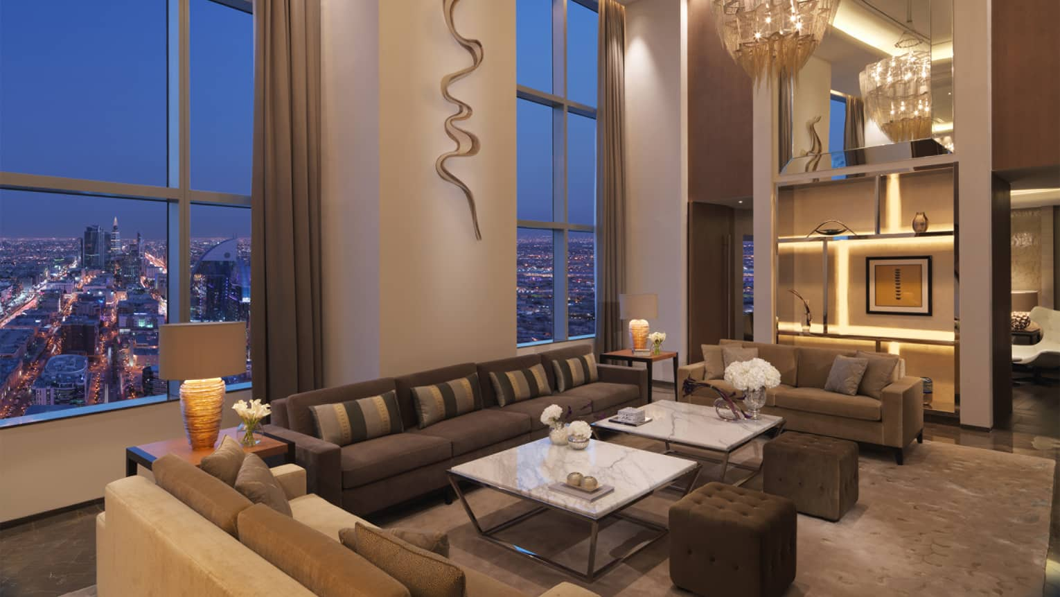 Seating lounge with long brown couches, white accent tables, and floor-to-ceiling windows
