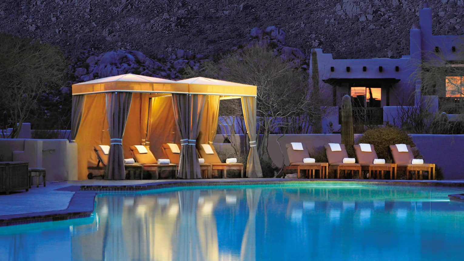 Lounge chairs with rolled white towels under illuminated poolside cabanas at night