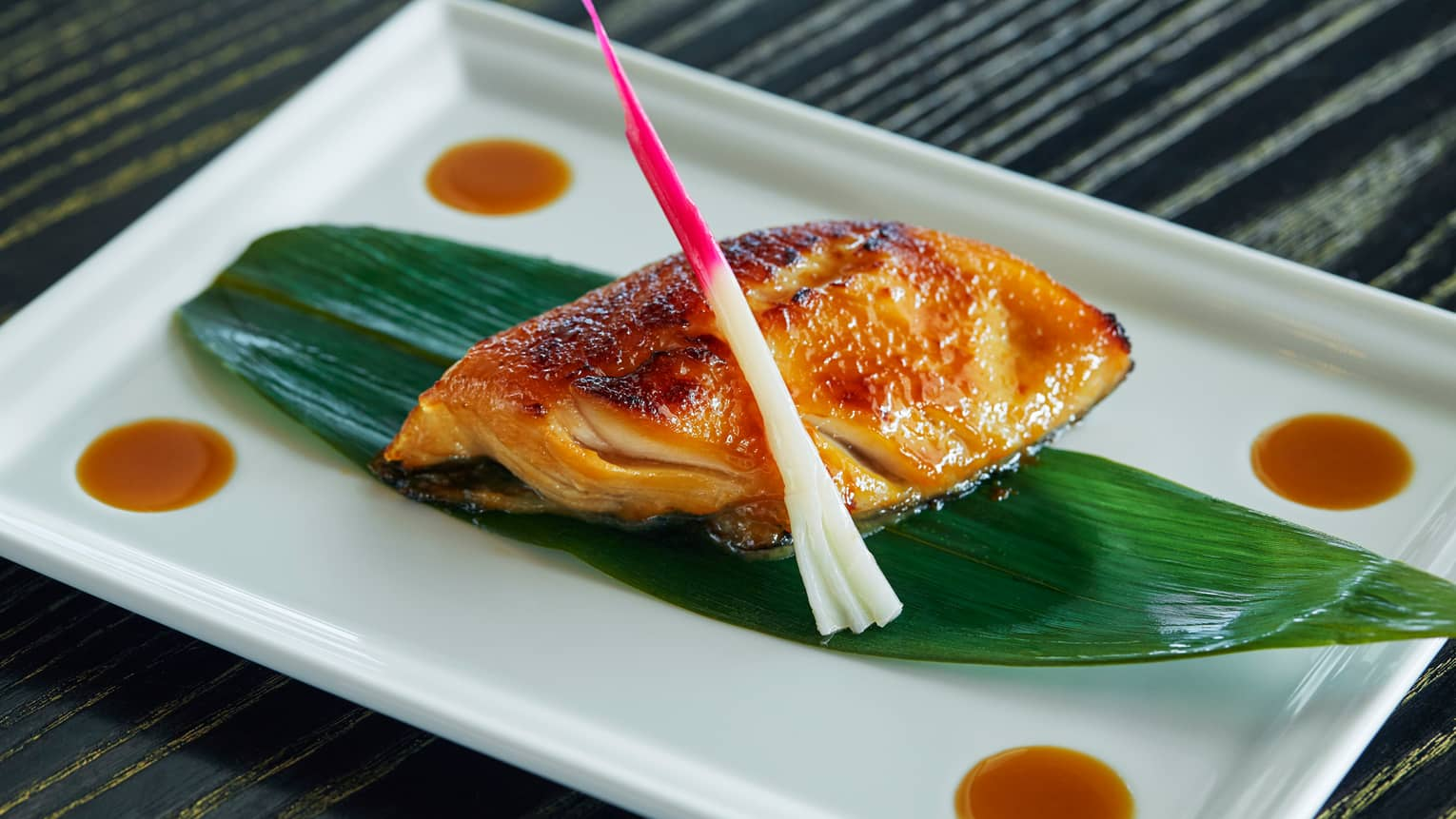 Black Cod Yuzu Miso fish fillet marinated, oven-baked on grilled seafood filet on leaf on white platter