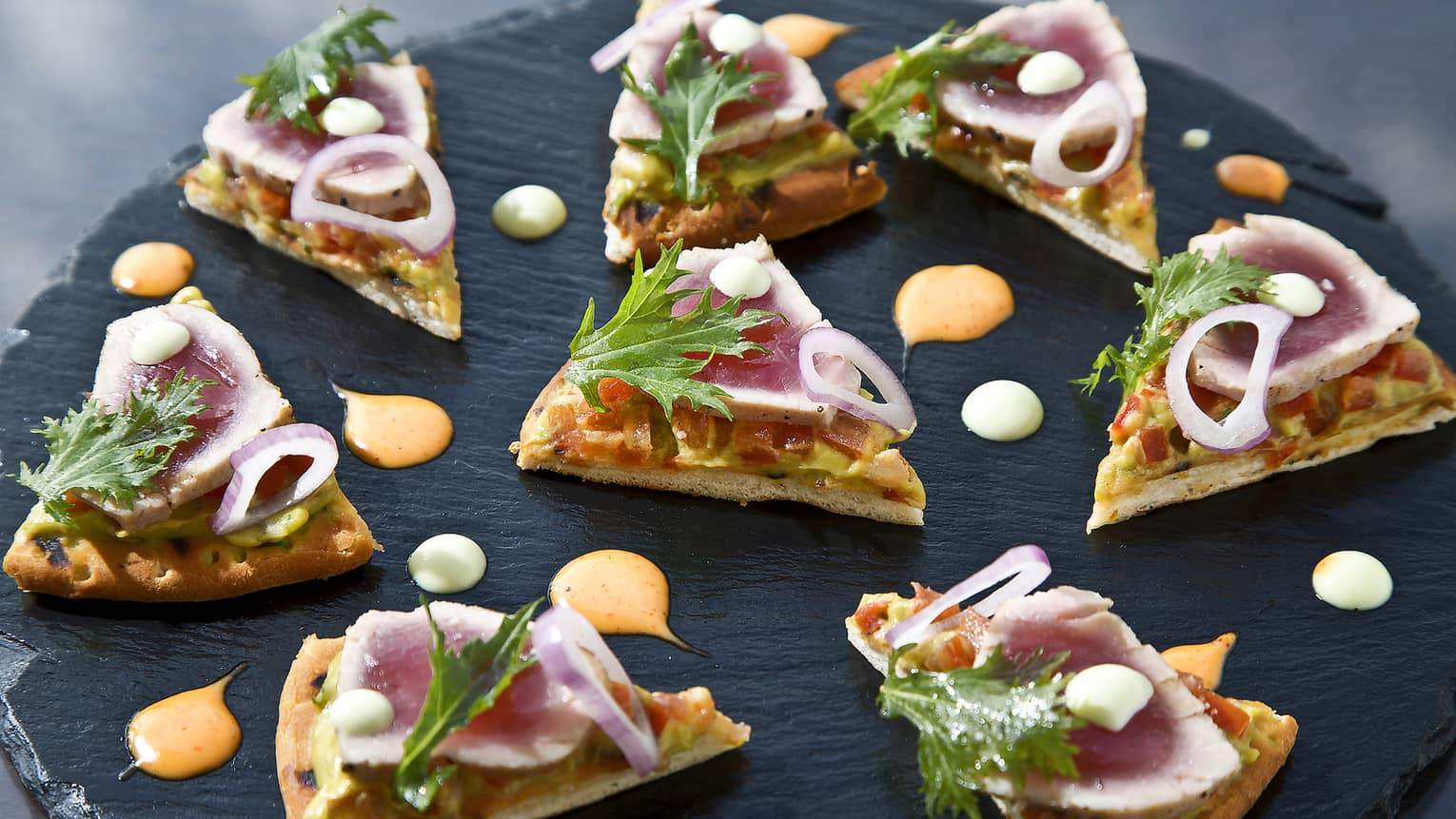 Small gourmet flatbread slices topped with red onion, greens on slate platter