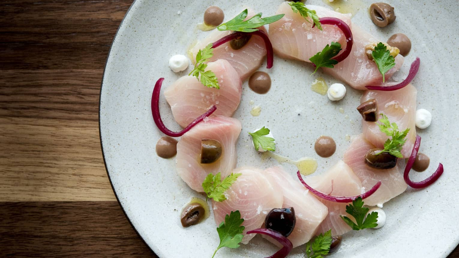 Hamachi Crudo slices of raw fish arranged in circle on plate with garnish