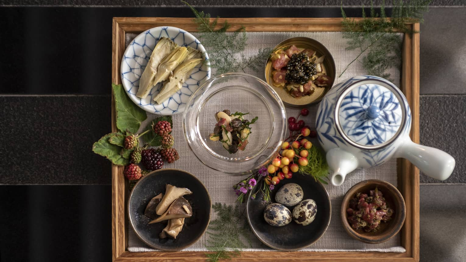 Aerial view of Sintoho wood dining tray, small dishes with quail eggs, artichokes, caviar, tea pot