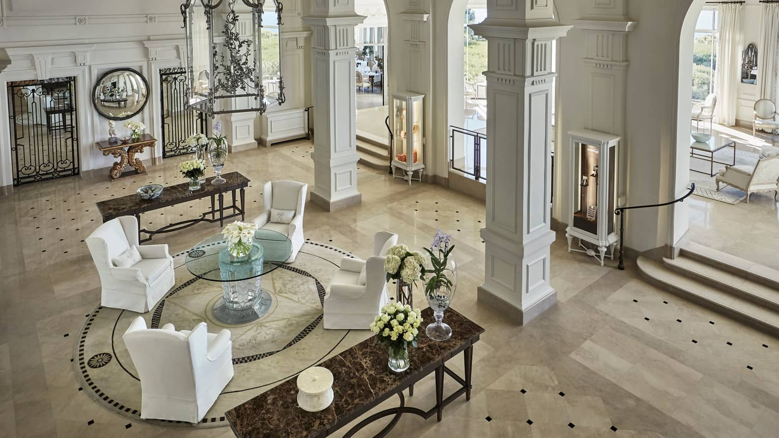 View of bright, palatial hotel lobby, white armchairs on marble floors under pillars