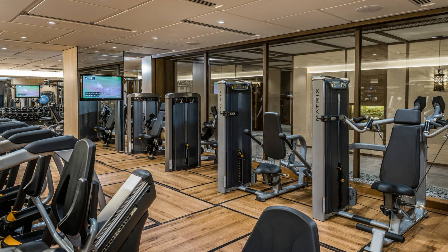 Cardio bikes, weight machines in front of glass wall in Fitness Centre