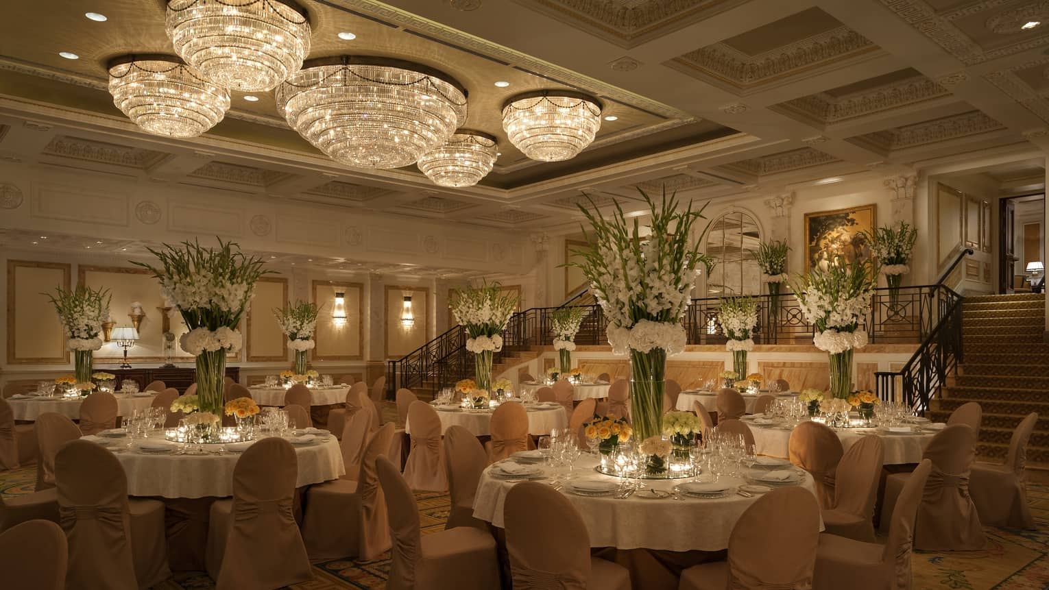 Ballroom banquet with round dining tables and chairs under small crystal dome chandeliers