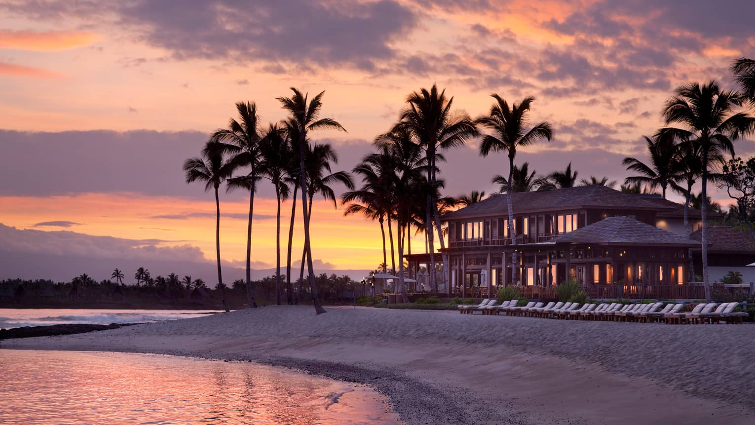 Silhouettes of Four Seasons Resort Hualalai building, tall palm trees on beach at sunset