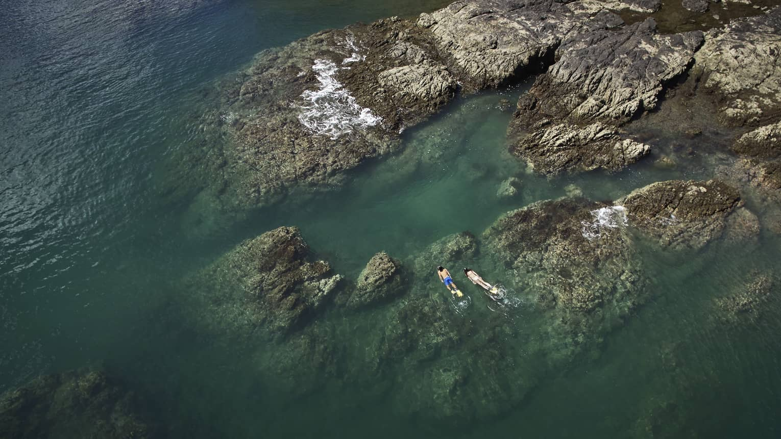 Aerial view of two people snorkelling by large rocks in the ocean