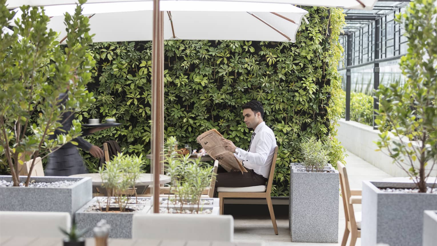 A guest reads a newspaper on an outdoor patio with foliage and umbrella covered tables.
