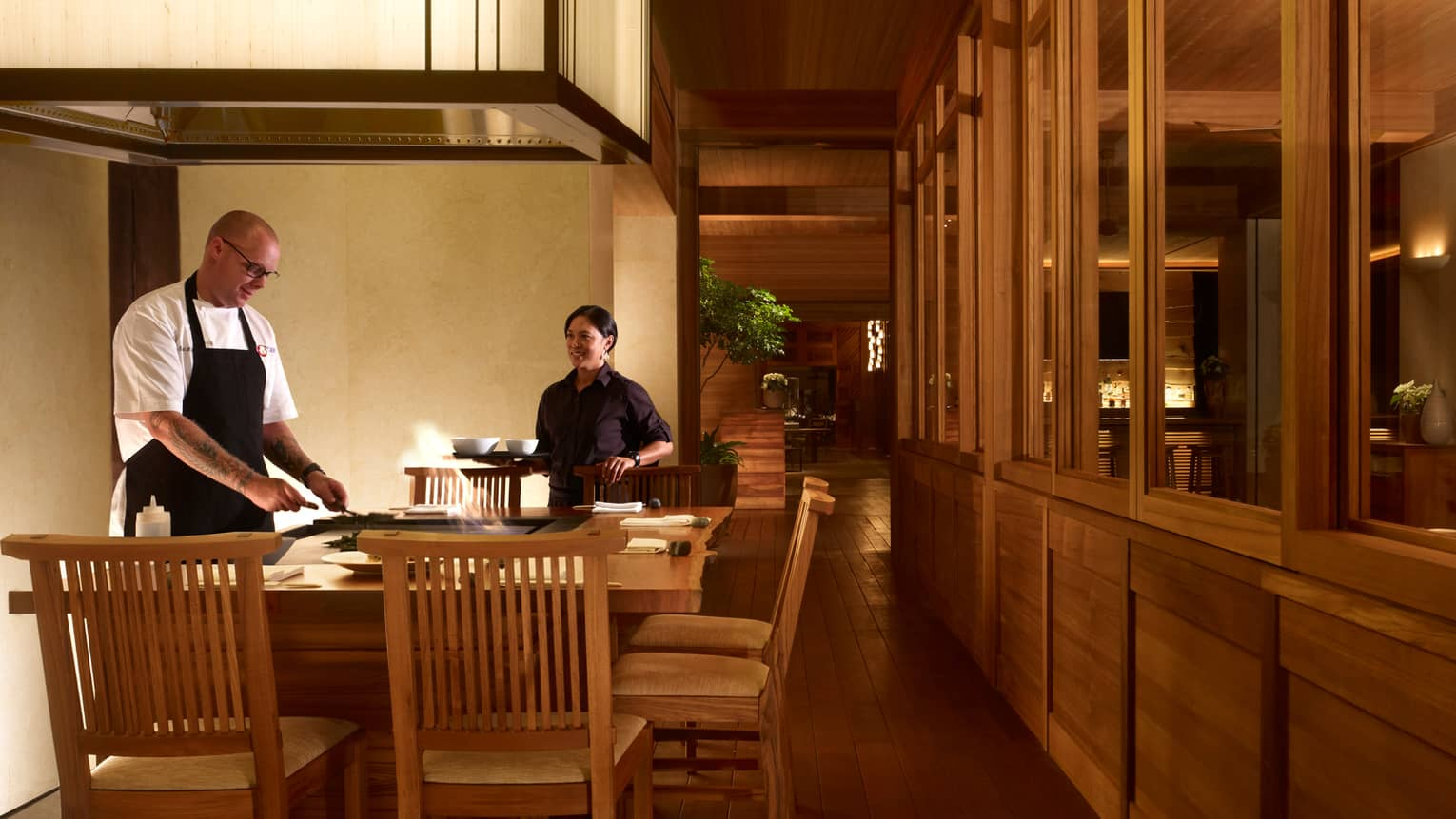 Chefs work at grill as flames leap out around him at small bar in NOBU restaurant