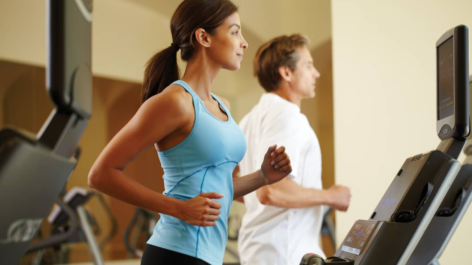 Woman in blue sleeveless shirt runs on treadmill beside man in T-shirt