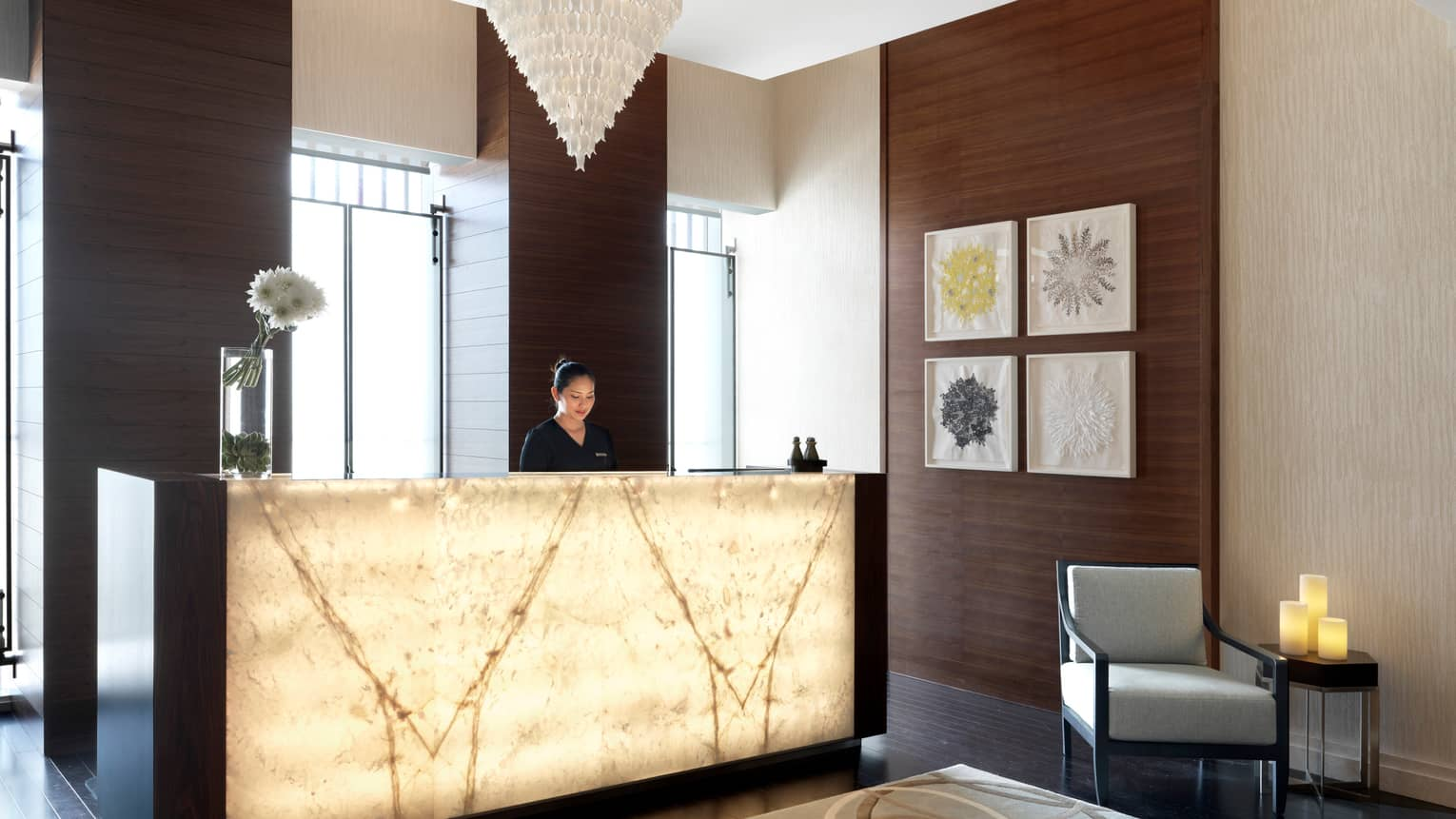 Woman stands at illuminated spa lobby reception desk in front of sunny windows