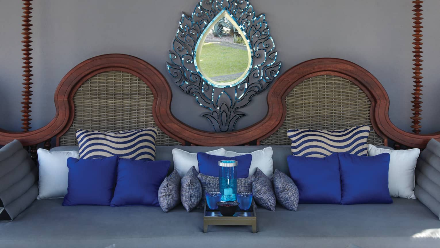 Teardrop-shaped mirror above wicker bench with decorative blue pillows, tray
