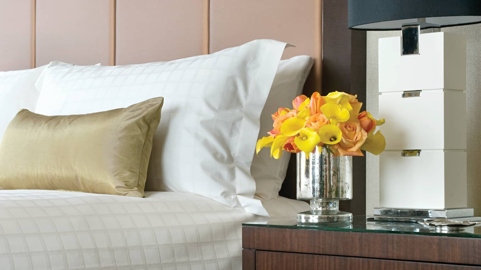 Premier Studio yellow, pink flowers in vase on nightstand by bed, gold pillow