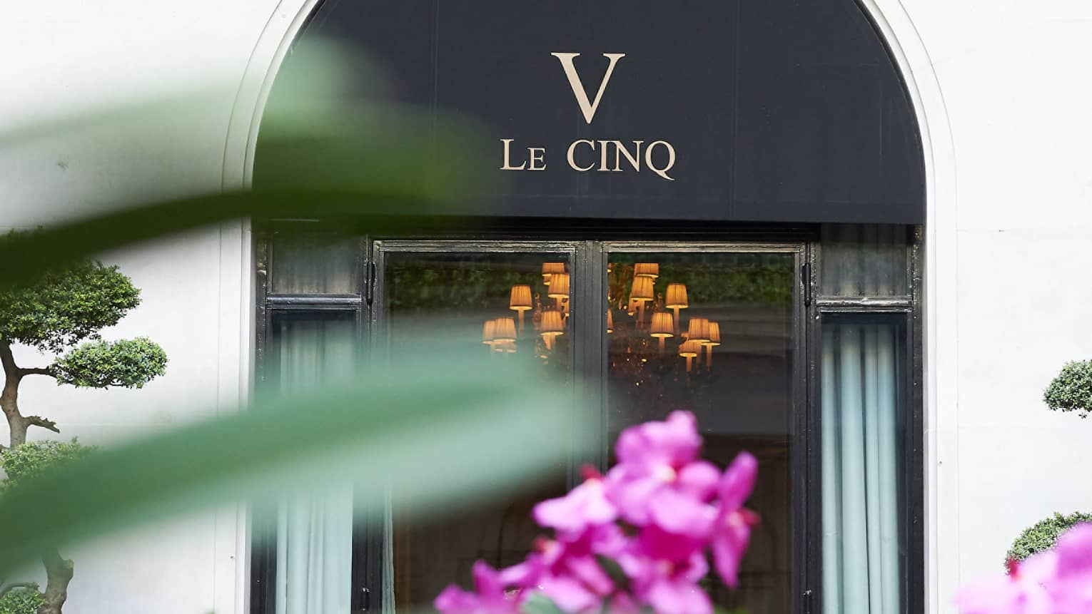 Le Cinq awning over entrance past purple flowers