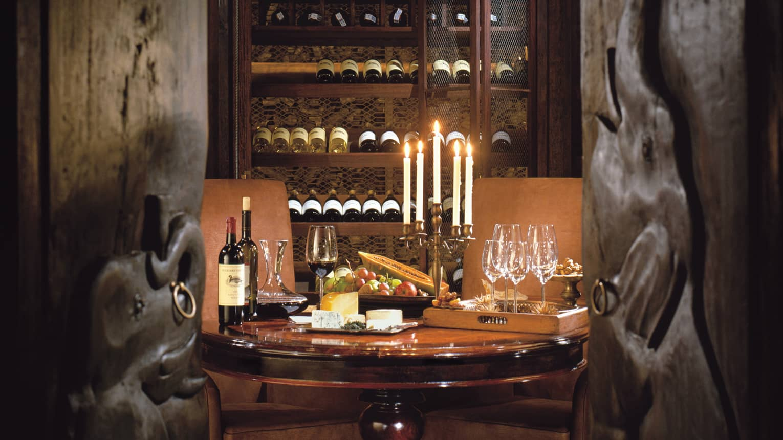 A dimly lit table for two with a candelabra and wine in a wine cellar
