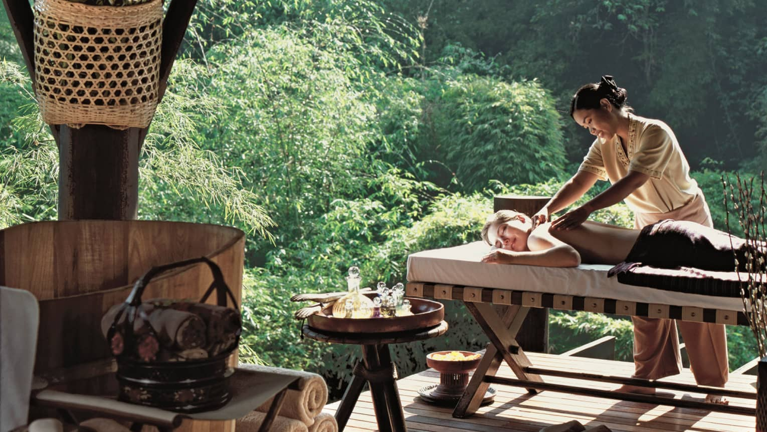 A four seasons staff massages a man in an outdoor spa room