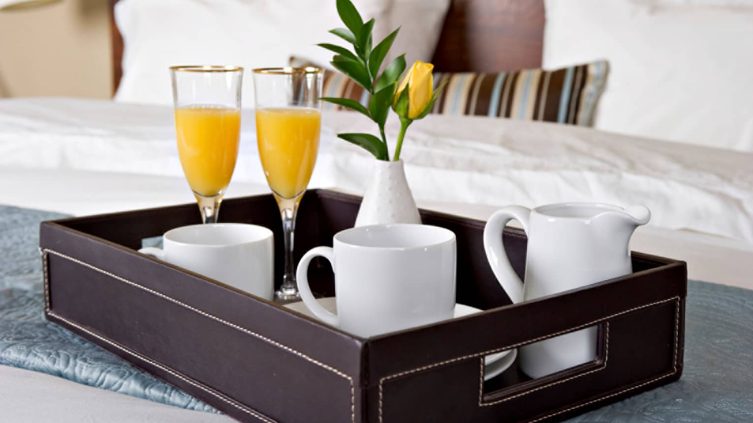Close-up of in-room dining tray with two champagne and orange juice glasses, white coffee mugs, yellow flower