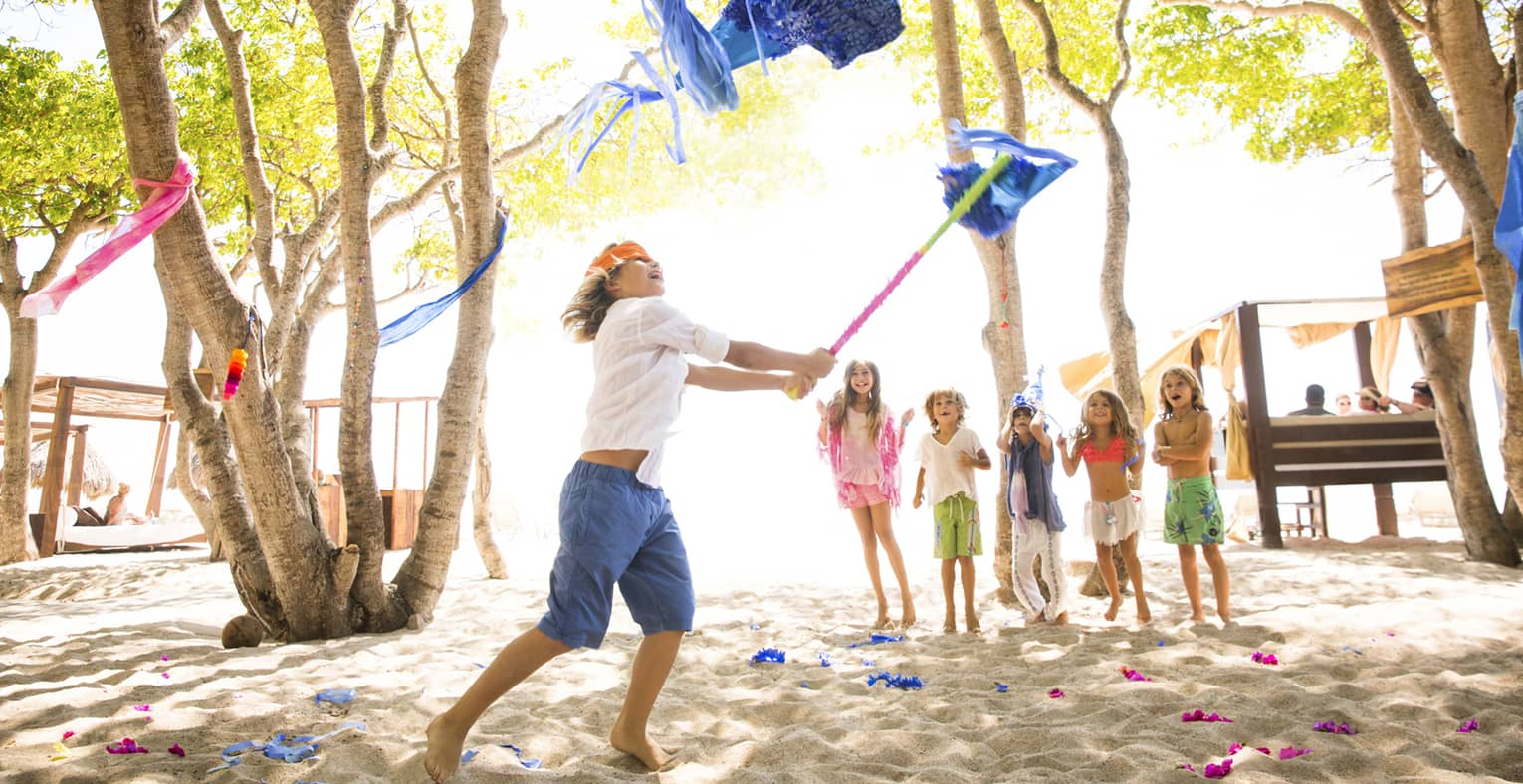 Boy wearing orange blindfold swings stick at blue pinata on beach while five young children cheer him on