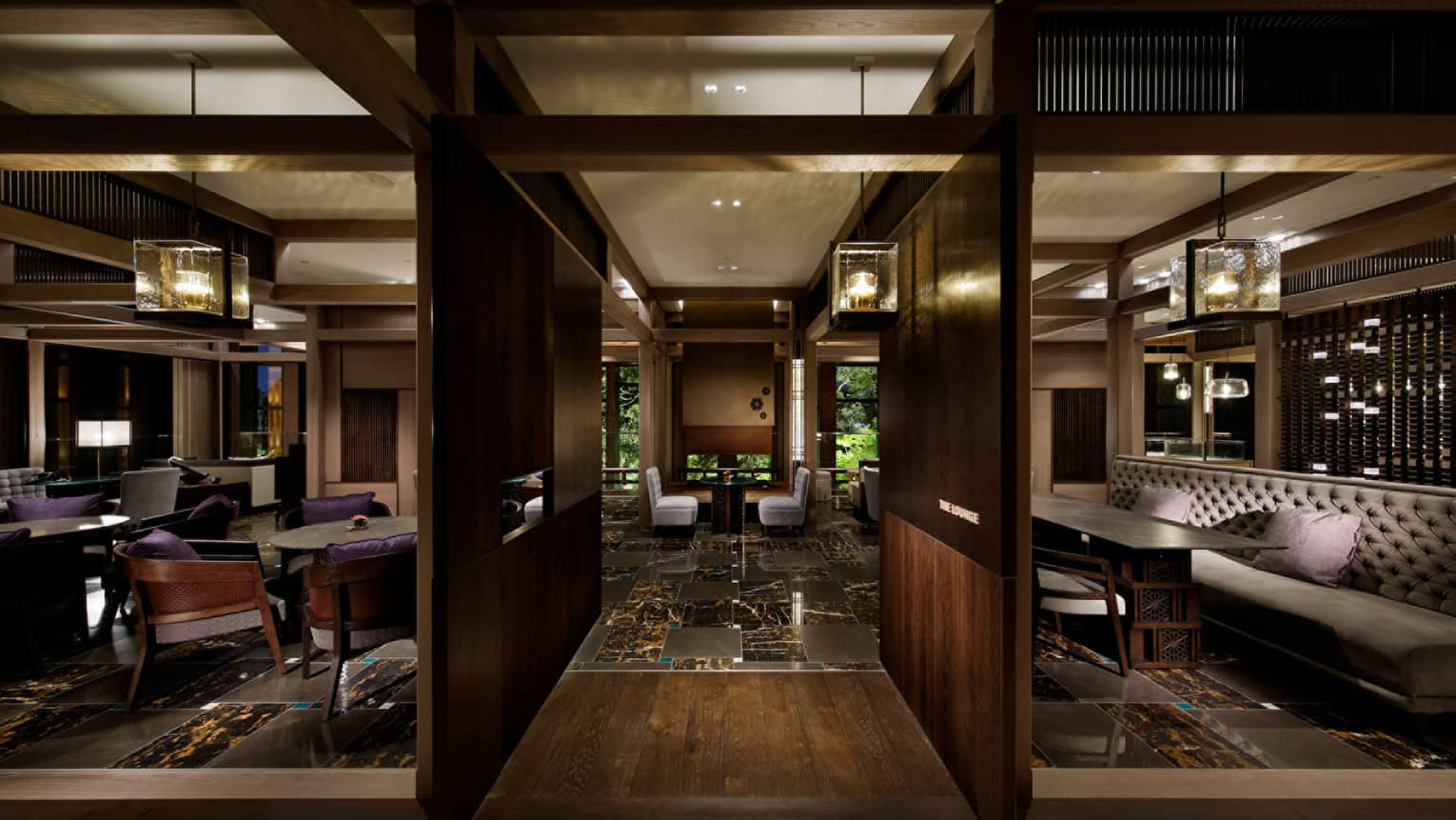The Lounge dark wood walls, beams, black marble floors, thick glass chandeliers